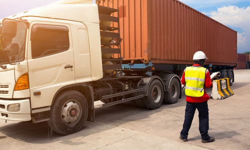 Image of a worker inspecting a transportation truck